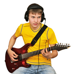 A young man plays the electric guitar
