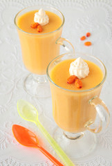 Two glass goblets with mousse of sea-buckthorn and whipped cream