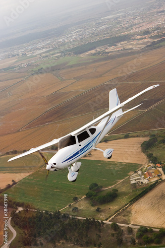 Small airplane flying over farm