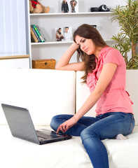young beautiful smiling woman prints on the laptop - indoors