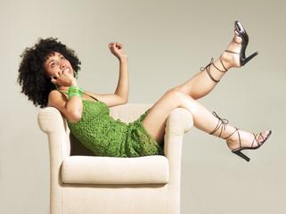 Joven mujer afroamericana al teléfono en un sofá.