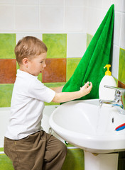 boy wipes hands a terry towel after washing