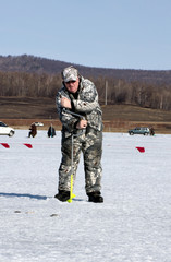 The man on the ice fishing with a hand auger