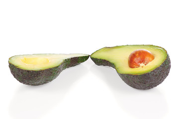 Halved fresh avocado on a white background