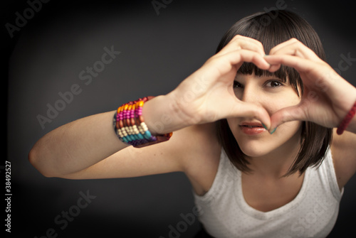 Beautiful girl forming heart with her hands