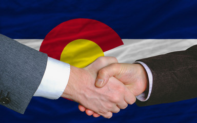 in front of american state flag of colorado two businessmen hand