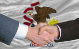 in front of american state flag of illinois two businessmen hand