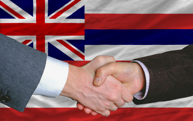 in front of american state flag of hawaii two businessmen handsh