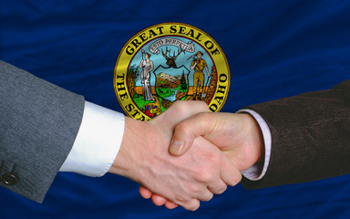 in front of american state flag of idaho two businessmen handsha