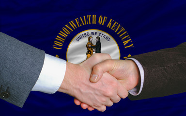 in front of american state flag of kentucky two businessmen hand