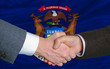 in front of american state flag of michigan two businessmen hand