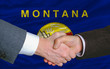 in front of american state flag of montana two businessmen hands