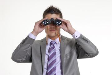 Joven ejecutivo sentado observando con binoculares.