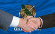 in front of american state flag of oklahoma two businessmen hand