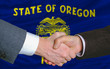 in front of american state flag of oregon two businessmen handsh
