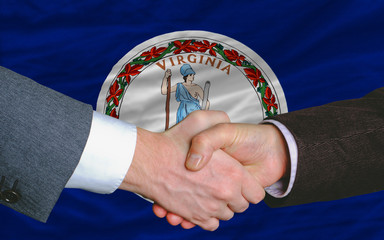 in front of american state flag of virginia two businessmen hand