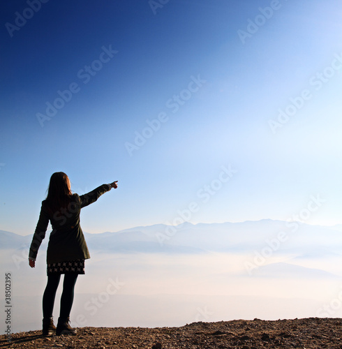 Young woman standing on cliff pointing on the sun