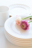 Cup and  plates with flowers on white background