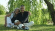 Senior couple sitting under a willow tree; Full HD Photo JPEG