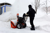 Snowblower in city under snowfall