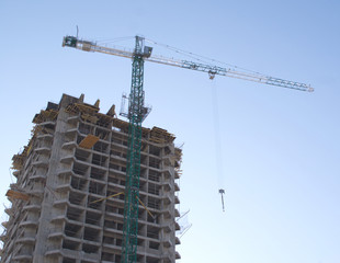 Сonstruction hoisting crane above building house over blue sky