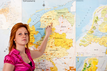 Teacher in classroom before a map of the Netherlands