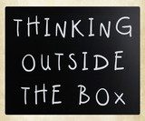 Thinking outside the box phrase, handwritten with white chalk on poster
