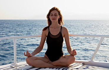 Young woman doing yoga meditation in lotus position