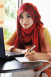 Beautiful muslim woman wearing red scarf ready to write