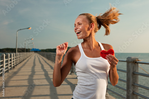 Beautiful woman in sunset light on a pier with watermelon heart
