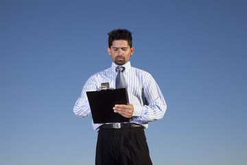 Powerful businessman holding a notepad