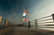 Young woman jumping in sunset light on a pier
