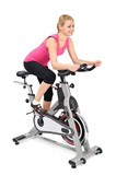 Fototapety young woman doing indoor biking exercise