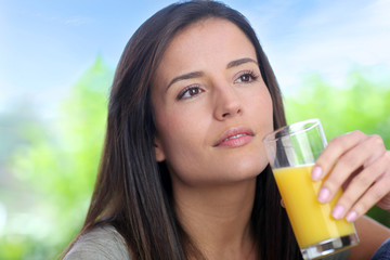 Young woman drinking fresh fruit juice