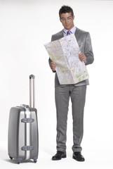 Joven ejecutivo viajando y leyendo un mapa.
