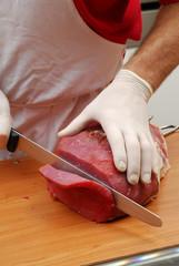 Cortando carne roja sobre una tabla de madera.