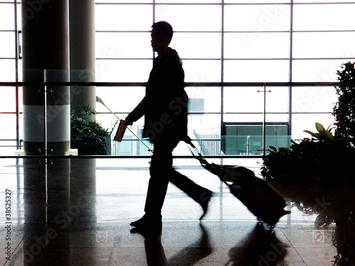 businessman walking in airport with suitcase