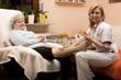 Altenpflegerin verbindet Seniorin das Bein