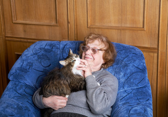 The old woman sits in an armchair and stroke a cat