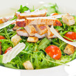 Chicken salad with tomatoes, arugula and bread croutons