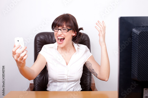 Young businesswoman screaming in rage after receiving bad news o