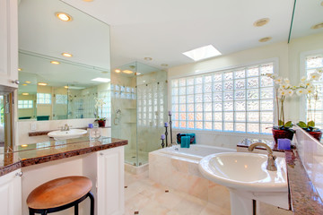 Large bright bathroom with double sinks and large tub.