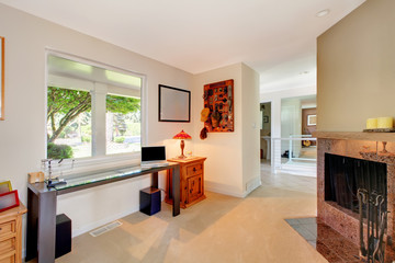 Home office with fireplace and window.with desk