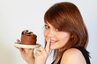 Jeune femme mangeant un gâteau au chocolat