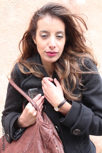Young working lady holding a bag and a smartphone, outside