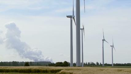 Windräder drehen vor Kohlekraftwerk im Wind