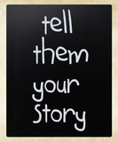 """Tell them your story"" handwritten with white chalk on a blackbo"