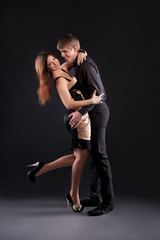 Sexy couple dancing on a black background