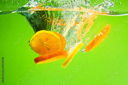 Leinwandbild Motiv YELLOW CITRUS SPLASHING IN WATER