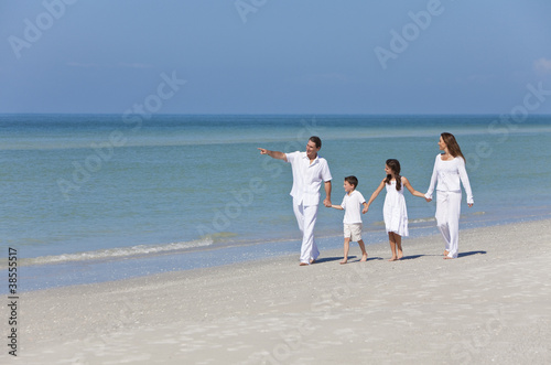 Mother, Father and Children Family Walking on Beach